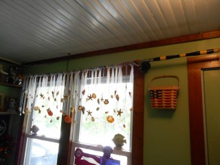 Re-purposed fishing poles as curtain rods, with tulle ribbons and seashell valance